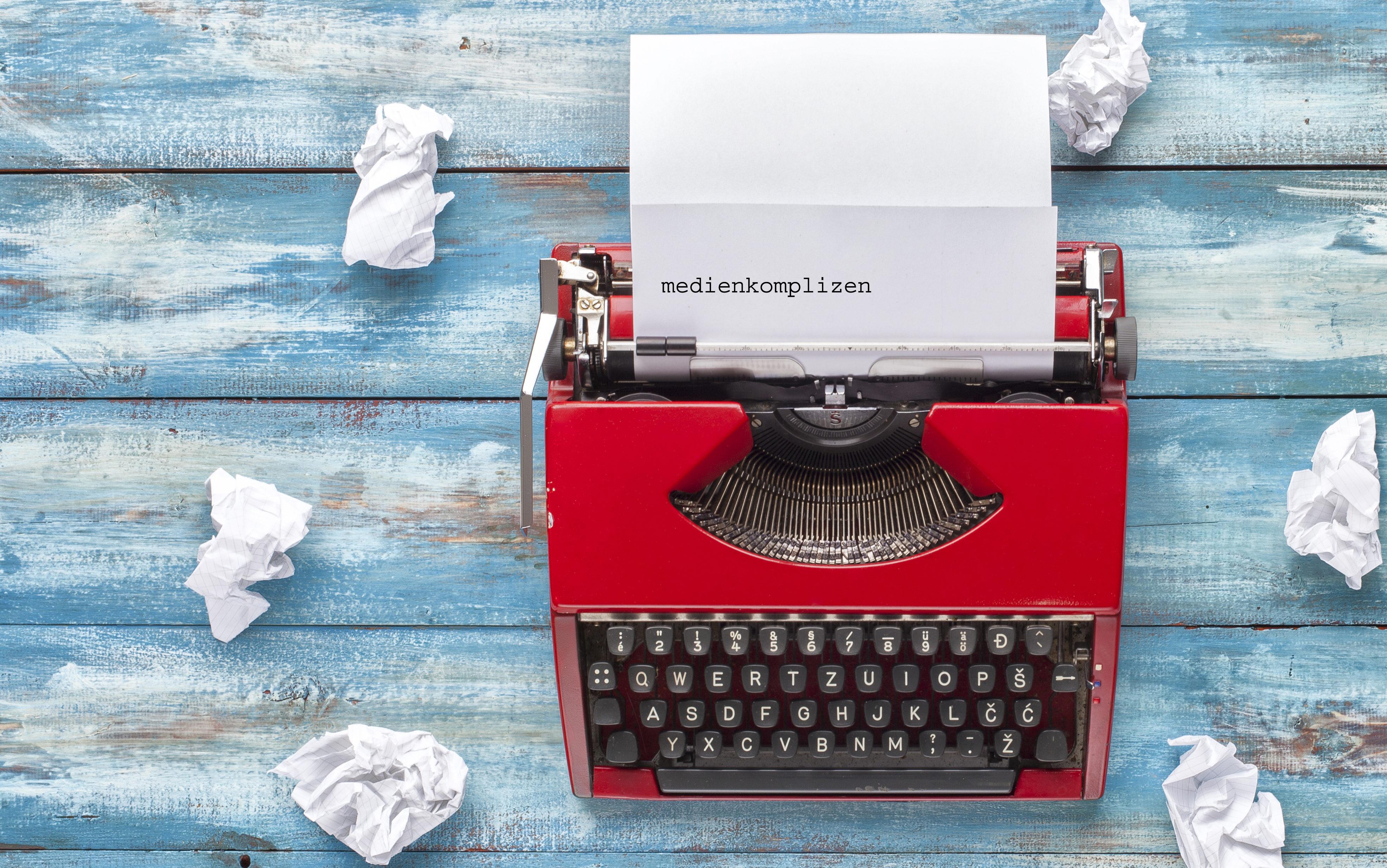 Schreibmaschine mit Blatt, auf dem getippt steht: medienkomplizen