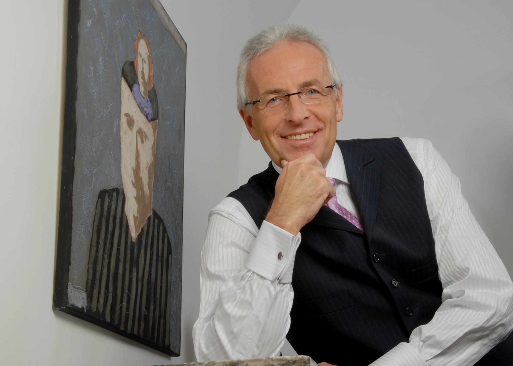 Lachendes Portrait von Günter Tengel, neben einem gemalten Portrait posierend