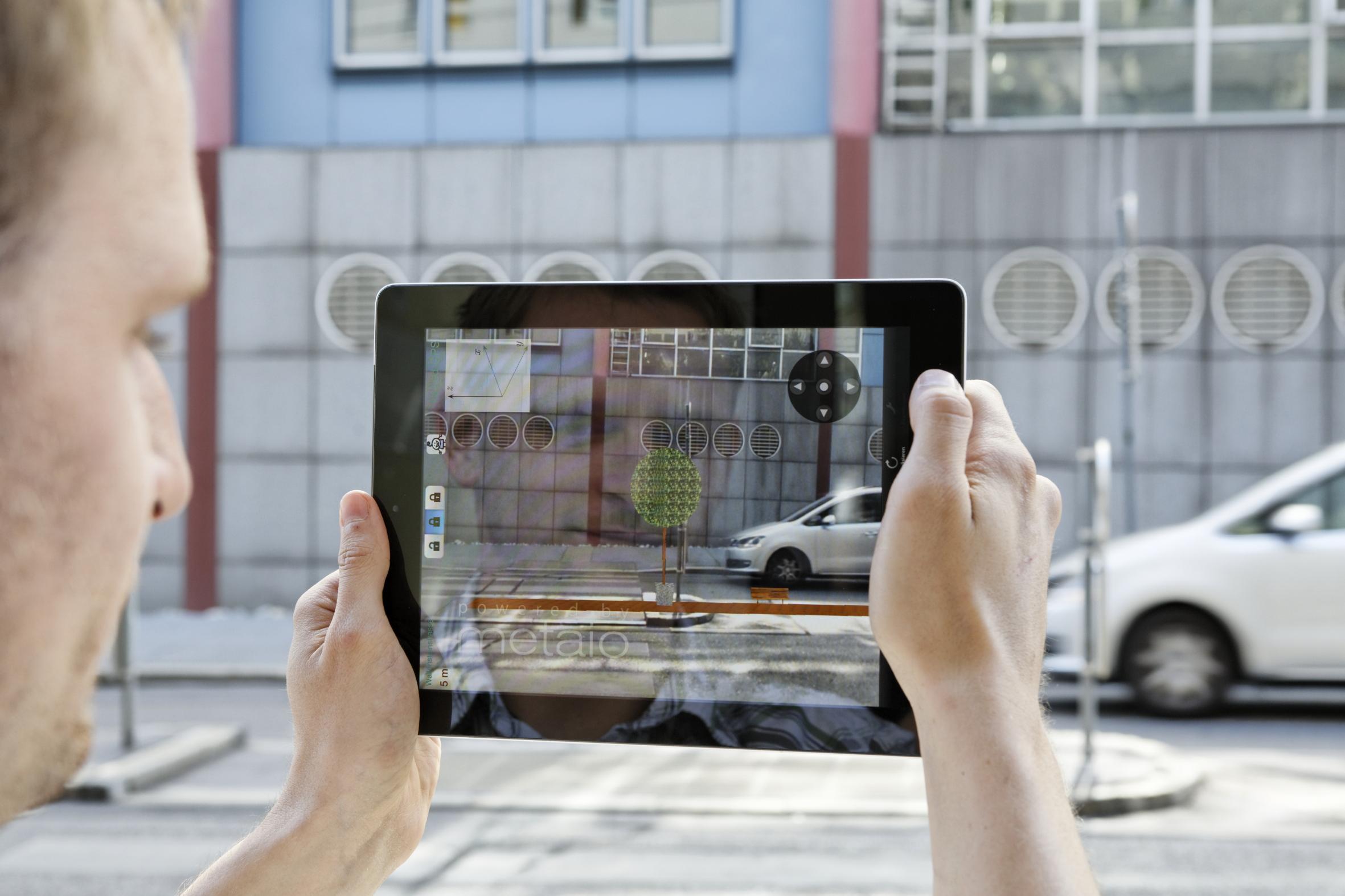 Forscher mit einem Tablet, das die App ways2gether zeigt, die Augmented Reality und Web 2.0 in partizipativen Verkehrsplanungsprozessen nutzt.