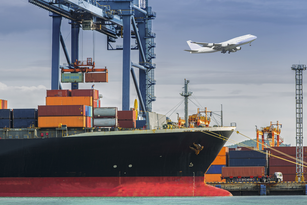 Containerschiff mit Fracht, im Hintergrund ist ein Flugzeug im Himmel zu sehen